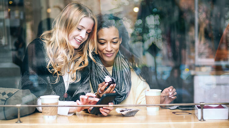 friends out to lunch looking at a phone app